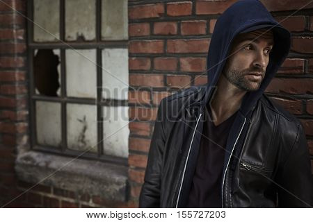 Handsome man in hooded top looking away