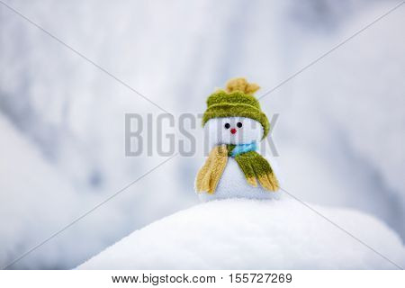On the white fluffy textured snow alone snowman the friend is standing in nice hat and scarf with red nose.