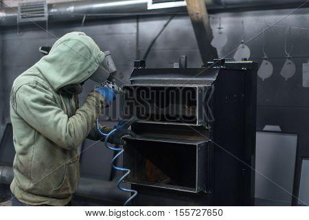 Man in green paints solid fuel boiler