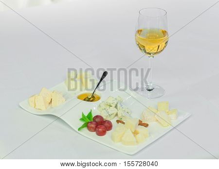 Cheese plate with cheeses Dorblu Parmesan Brie Camembert and Roquefort in serving on the table from an old tree close-up