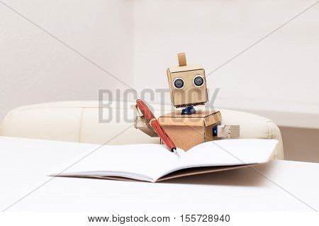 Robot writes with a ballpoint pen and sitting at the table