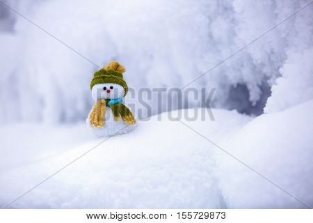 Snowman the Santa's assistant is standing in green hat wrapped with the scarf on nice textured snow on frosty winter morning.