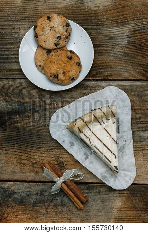 Beautiful Homemade Cake Cheesecake On A White Paper On The Wooden Background With Cinnamon Stick. Ne