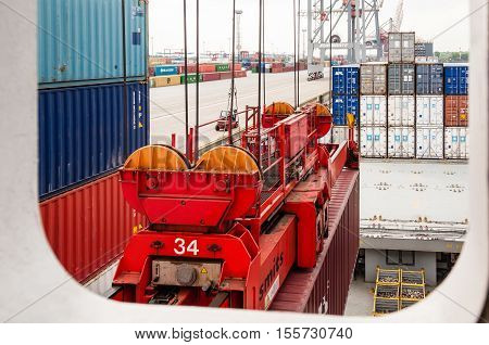 Hamburg, Germany - May 10, 2011: View out the porthole of a large container ship at the Container Terminal Buchardkai in Hamburg, Germany while being loaded with containers before leaving for its next trip.