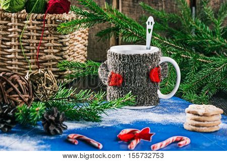 Mug with woolen warmer on the table with candy canes, cookies and christmas decorations