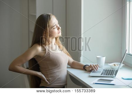 Profile Portrait Of A Young Woman, Stretching Working At Laptop