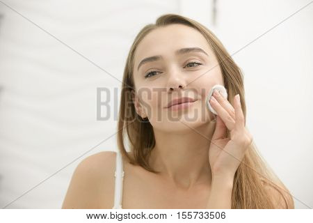 Smiling Young Woman Cleaning Her Skin With A Cotton Pad,
