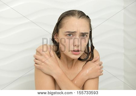 Young Woman Shivering With Cold In The Shower