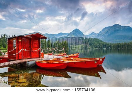 The picture captures the view of a person watching boats reverie calm lake fantastic mountains and the clouds floating across the sky
