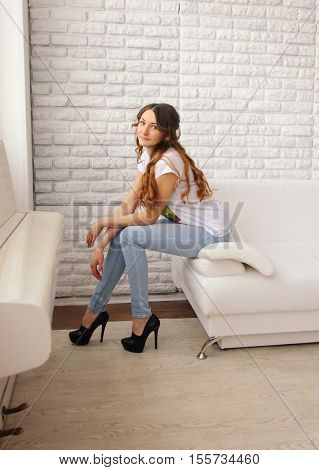 Girl in jeans sitting on the sofa