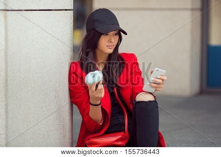 Young pretty businesswoman texting outdoors on mall steps and eating donut. Beautiful young stylish asian woman in red casual suite and glasses with phone and fast food sitting against street background
