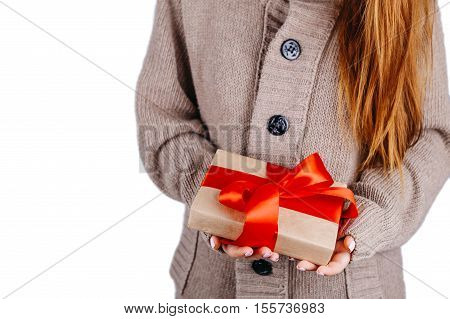 Woman in knitted sweater holding a present, Gift is packed in craft paper with pine cones and tied with red ribbon. DIY way to wrap a present.
