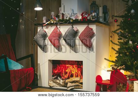 Christmas Socks With Gifts On The Fireplace. Christmas Warm Cozy Interior Room, In Anticipation Of T