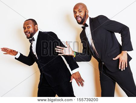 two afro-american businessmen in black suits emotional posing, gesturing, smiling. wearing bow-ties lifestyle