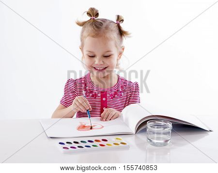 Happy cheerful baby girl child drawing red heart with brush in album with painting tools laughing isolated on a white background