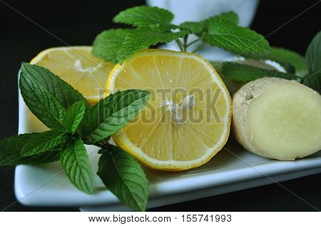 Cough and cold home remedy with lemon, ginger, mortar and pestle with dried calendula and fresh mint on black background and copy space