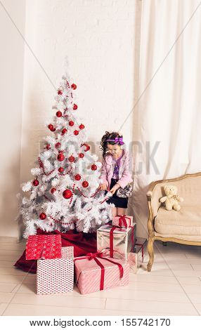 8 years old little girl decorating Christmas tree at home