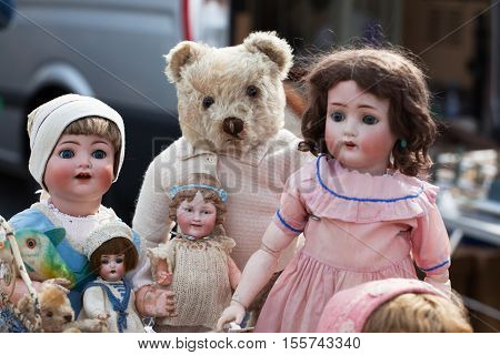 bunch of old dolls with teddy at a flea market