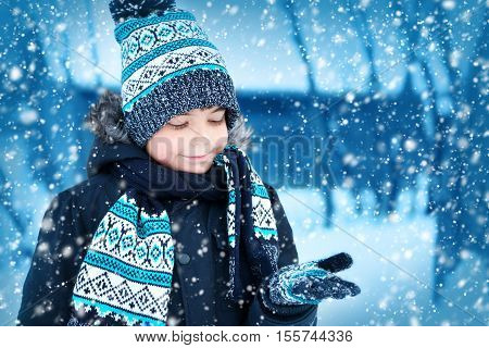 Boy in knitted hat, gloves and scarf outdoors at snowfall. Child in winter clothes
