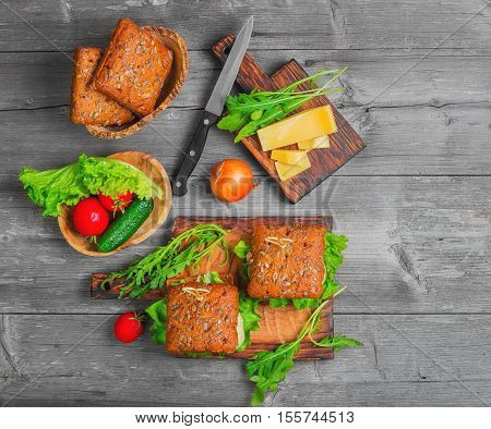 Two sandwich burger with meat and vegetables. Ingredients for cooking sandwiches burgers and fresh vegetables cucumbers tomatoes lettuce. Sandwich sauce. Gray background. Top view blank space.