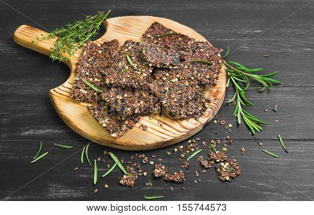 Bread crackers from grain flax seeds sesame spices wooden board healthy food. Broken pieces grain Bread crackers flax seeds. Spices for flax crackers grain breads thyme rosemary. Black background