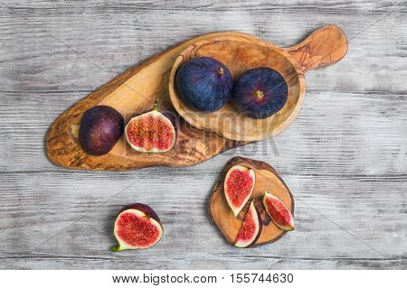 Violet Blue figs whole fruit figs cut into pieces on a board of wood of olive light white wooden background. Top view.