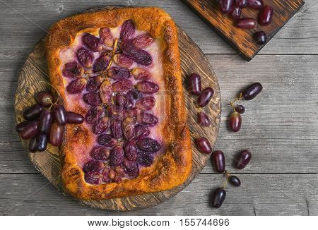 Homemade Galette or crusty pie with purple grapes. Grapes for pie on board. Grapes on the table. Gray wooden background. Top view