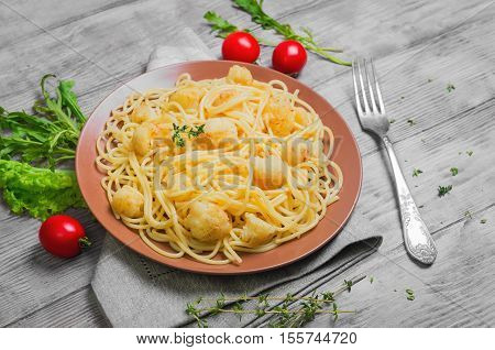 Italian pasta spaghetti on brown plate with cauliflower. Green Spaghetti with Cauliflower thyme lettuce cherry tomatoes cloth. Light white wooden background.