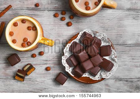 Traditional German domino stein chocolate gingerbread cakes with marzipan and jelly filling. Hot chocolate cocoa two cups. Chocolate balls for domino stein gingerbread and hot chocolate. Top view