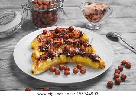 Bananas baked grilled cottage cheese sauce with ice cream chocolate white plate. Chocolate cereal balls chocolate sauce ice cream cottage cheese in glass bowl. Light wooden table background.