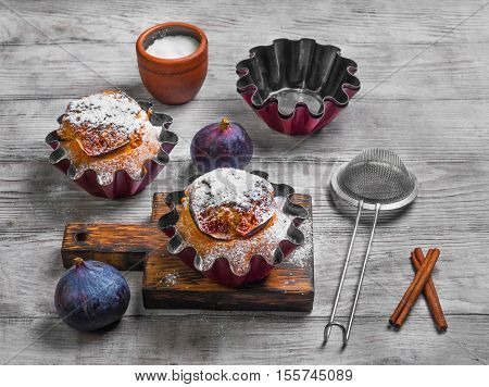 Baked Muffins cake with figs sugar powder. Fresh fruit muffin figs. Metal molds for muffins cinnamon board. Light white wooden background.
