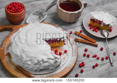 Christmas New Year winter pie cake with red berry cranberries cover white whipped meringue icing tea. Slice winter Christmas pie cake on plate. Cranberry for winter pie. Light wooden background.
