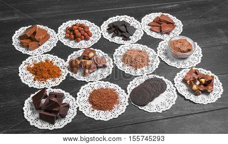 Chocolate assortment ingredients texture. Cocoa powder cocoa mass chocolate paste chocolate candy chocolate cookies broken chocolate almonds hazelnuts Dark black wooden background
