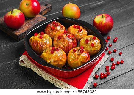 Baked apples baking in oven. Fresh apples for baking on board. Caramel sauce for baked apples red berries. Dark black wood background. Garden apples.