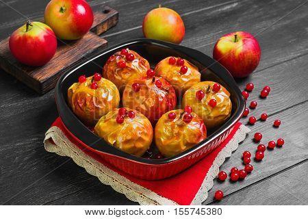 Baked apples baking in oven. Fresh apples for baking on board. Caramel sauce for baked apples red berries. Dark black wood background. Garden apples.