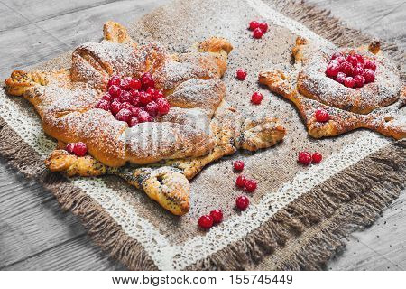Sweet pastry buns danish in form of Christmas snowflakes powdered sugar. Light white wooden background. Concept snow for Christmas cards. Red berries of cranberry buns for snowflakes danish.