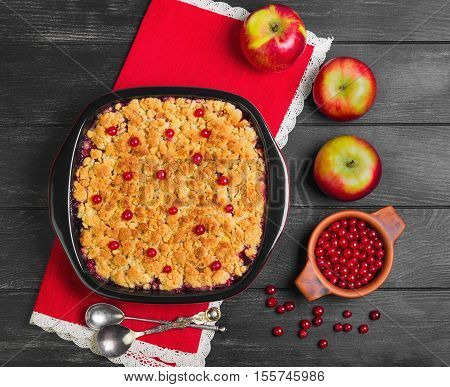 Dessert pie crumble cake apples red berries cranberries. Fresh apples berries for pie crumble cake cloth. Red Black ceramic baking pan cake crumble. Wooden dark background. Top view.