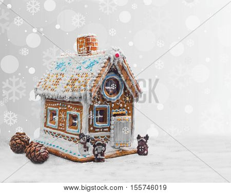 New Year Christmas gingerbread house decorated with icing sugar snow. Christmas figure Santa Claus reindeer snowman next to gingerbread house. Christmas rooster symbol of new year gingerbread house.