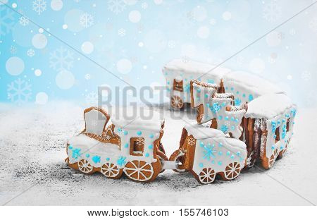 New Year card with Christmas sweets toy. Gingerbread cookie in the form a Christmas train. Gingerbread Christmas tree on the train. Snow background with snowflakes blue white icing on steam train.