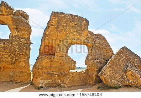 The remains of the ancient huge rock walls with arches for tombs known as Arcosolia Agrigento Sicily Italy.