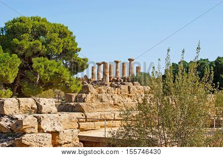 The tall columns of the Temple of Heracles behind the stone ruins in Valley of the Temples Agrigento Sicily Italy.