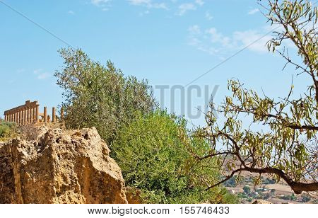 The view on the colonnade of Juno Temple behind the massive boulder on territory of archaeological site Agrigento Sicily Italy.