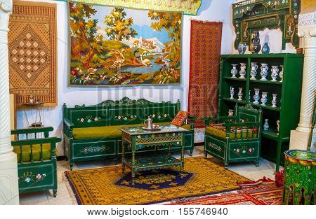 KAIROUAN TUNISIA - AUGUST 30 2015: The tea room in Mansion of Governor decorated with green wooden furniture carpets and porcelain vases on August 30 in Kairouan.