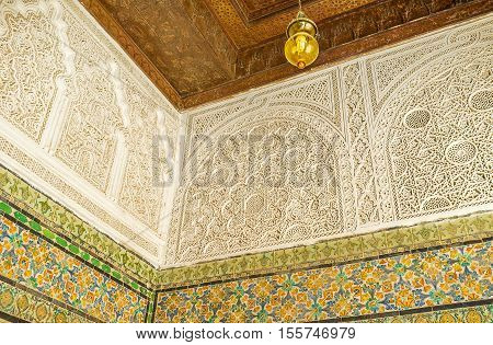 KAIROUAN TUNISIA - AUGUST 30 2015: The walls of Zaouia Sidi Sahab (Barber's Mosque) decorated with fine Islamic patterns on glazed tiles carved wooden details and fretwork on August 30 in Kairouan.