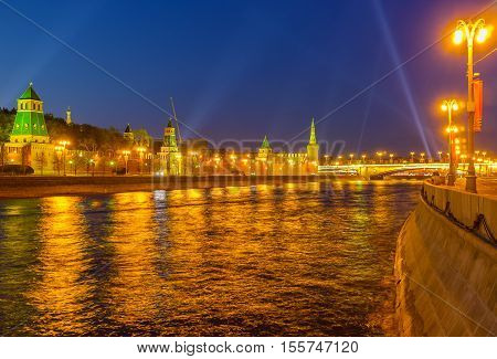 The Moskva River becomes golden in bright illumination of its embankments Kremlin wall and towers Moscow Russia.