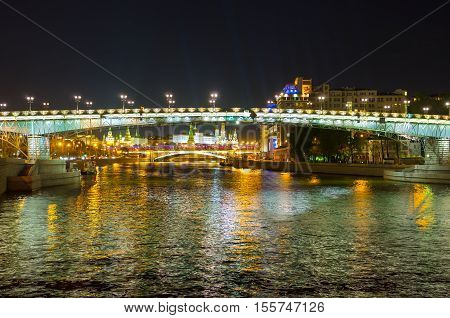 The night walk along the Moskva River with the view on bright illuminated Patriarshy and Greater Stone Bridges and the towers of Moscow Kremlin Russia.