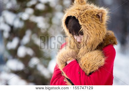Portrait of unhappy beautiful young woman wearing red winter coat and funny fur hat and mittens walking outdoors, feeling cold in wintertime, rubbing shoulders trying to keep warm, copy space