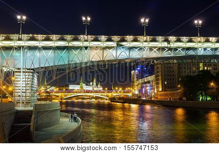 The Patriarshy and Greater Stone Bridges over the Moskva River in bright lights with the towers and Palace of Kremlin on background Moscow Russia.