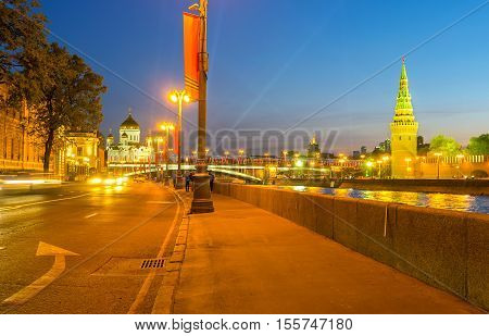 The evening walk along the Moskva river at Sofiyskaya embankment with the view on Vodovzvodnaya Tower of Kremlin and Cathedral of Christ the Saviour Moscow Russia.