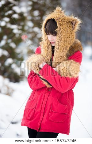 Portrait of unhappy beautiful young woman wearing red winter coat and funny hat and mittens walking outdoors, feeling cold in wintertime, rubbing her shoulders trying to warm up